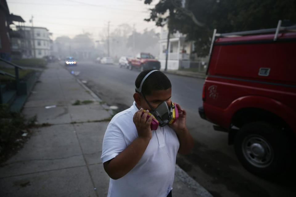A boy used a mask to protect himself from heavy smoke from a fire on Bowdoin Street in Lawrence.
